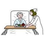 病院のベットで食事をする男性患者と看護師の女性