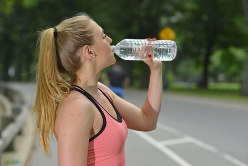 ランニングの途中で水を飲む女性